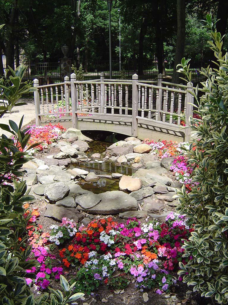 bbin快速厅花园,一座小桥俯瞰鲜花和一个池塘在威斯敏斯特公园bbin出租