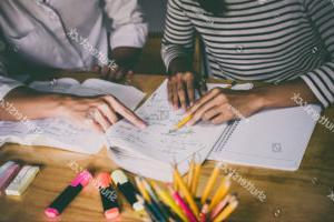 两个学生一边做作业,一边用铅笔和荧光笔