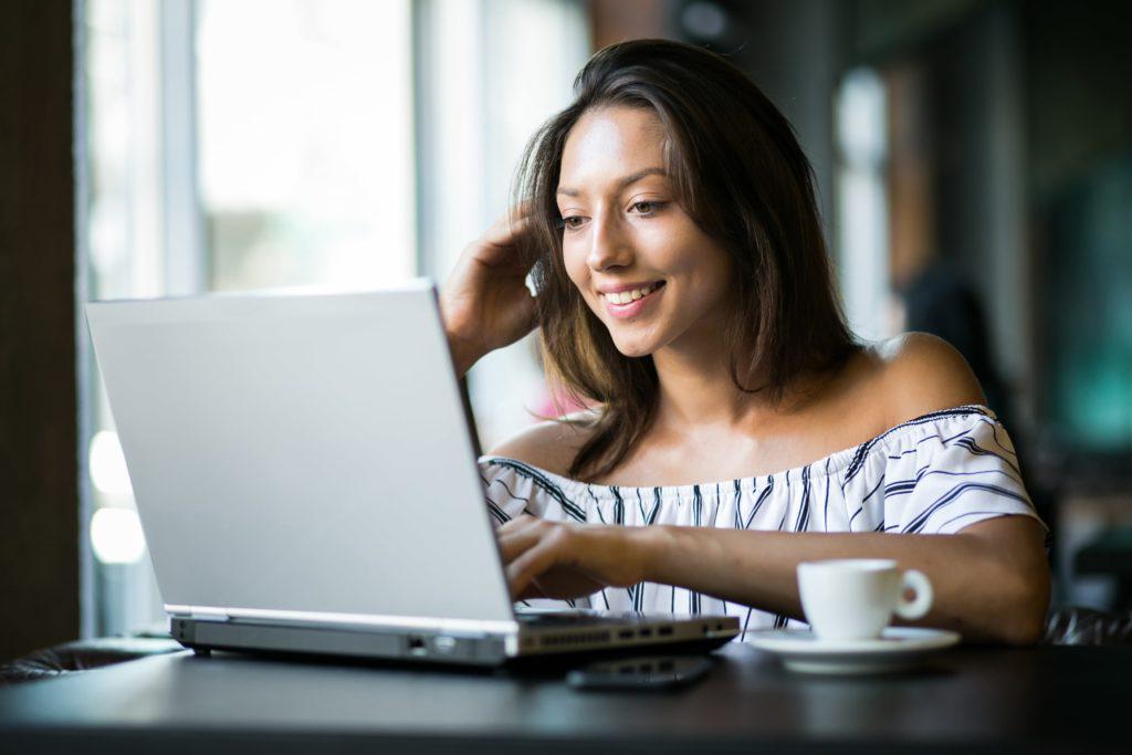年轻女子在电脑前喝咖啡