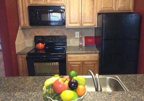 在Haverford法院出租的bbin里,厨房里有黑色的电器和一个水果盘