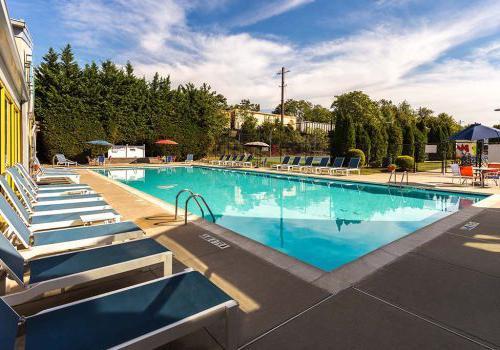 帕克公园Enclaves的户外游泳池,配有躺椅和雨伞