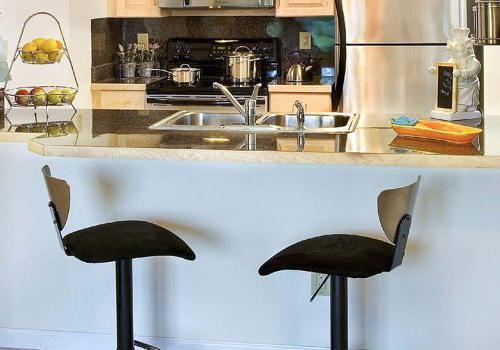 帕克公园的 Enclavesbbin的一间带电器和两把黑色椅子的厨房出租