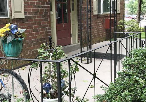 在Westgate Arms出租的bbin里,有一个带门廊和鲜花的住宅楼入口