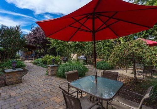 有桌子的户外座位区, 椅子, 以及在帕克公园的门户大厦出租的红色雨伞