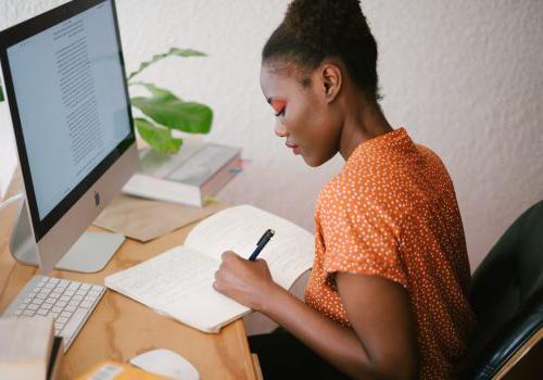 在喷泉花园出租bbin里,一个女人一边用电脑工作一边在笔记本上写东西